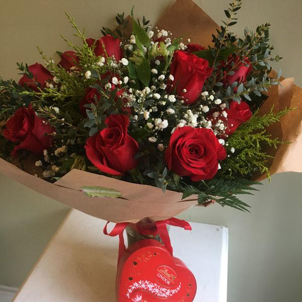valentines dozen red roses in vase with chocolates