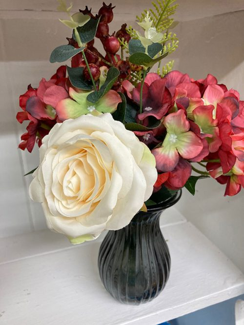 rose with hydrangea and berries on black vase