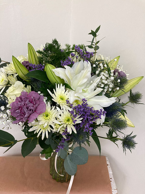 Seasonal flowers in whites and lilac in vase